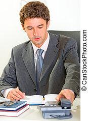 Sitting at office desk modern businessman pick up phone -...