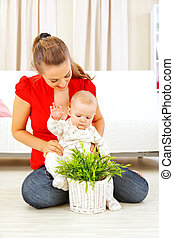 Smiling mommy showing plant to her baby