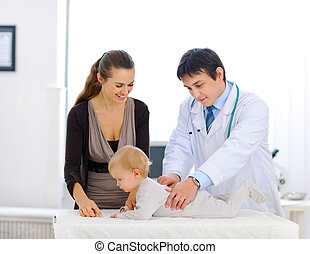 Cute baby being checked by a pediatric doctor