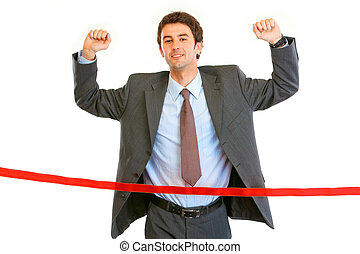 Pleased businessman crossing finish line isolated on white....