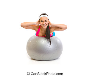 Smiling fit girl making exercise on fitness ball