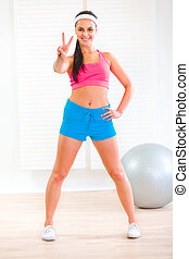 Smiling  young  girl in sportswear showing victory gesture at living room