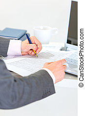 Closeup on hands of businessman writing in document