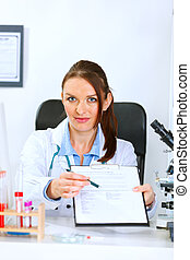 Medical doctor woman sitting at office table with document...