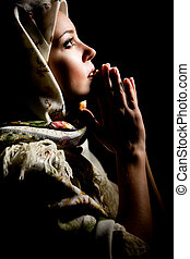 Portrait of beautiful praying girl with old russian shawl on...