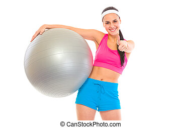 Smiling fit young girl with fitness ball showing thumbs up gesture isolated on white