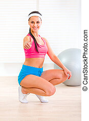 Smiling fitness young girl squatting down and showing thumbs...