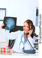 Smiling medical doctor woman talking on phone and holding...