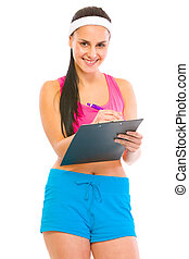 Smiling female fitness trainer writing in clipboard