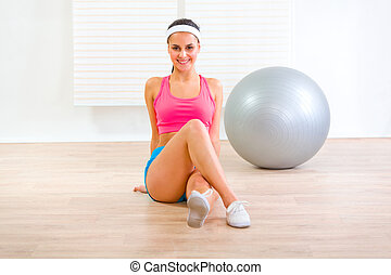 Happy young woman making gymnastics exercise