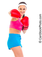 Cheerful fit young girl in boxing gloves punching isolated on white