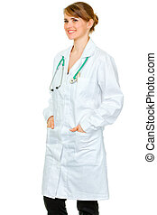 Smiling medical female doctor with hands in pockets of robe looking at copy space isolated on white