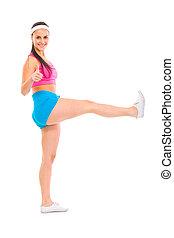 Full length portrait of smiling fitness girl with raised leg...