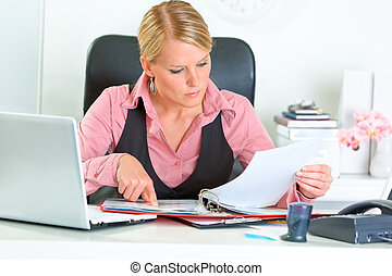 Concentrated modern business woman sitting at office desk...