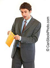 Shocked modern businessman checking parcel