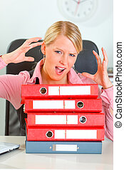 Stressed modern female manager with pile of folders at...