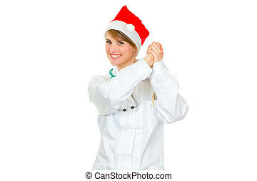Smiling female medical doctor in Santa hat showing partnership gesture isolated on white
