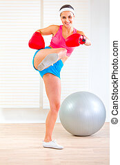 Smiling fitness girl in boxing gloves kicking - Smiling...