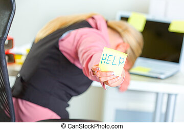 Tired business woman showing sticky note with help word -...