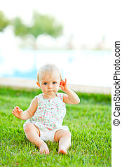 Portrait of adorable baby sitting on grass