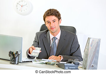 Modern businessman sitting at office desk and giving money...