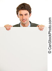 Handsome guy holding blank billboard isolated on white
