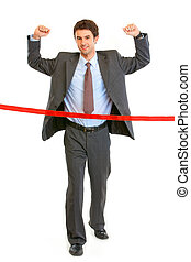 Full length portrait of pleased businessman crossing finish...