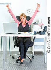 Excited modern business woman sitting at office desk and...