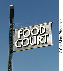 FOOD COURT SIGN - A food court sign on a pole against a blue...