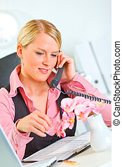 Happy business woman carefree talking phone in office