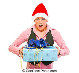 Surprised modern business woman in Santa Hat looking on gift