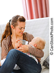 Young mother sitting on sofa and feeding her baby  at home