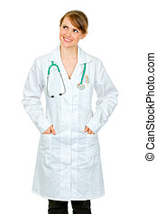 Smiling medical doctor woman with hands in pockets of robe looking at copy space isolated on white