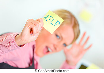Stressed business woman showing sticky note with help word -...