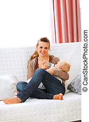Young mother sitting on sofa and feeding her baby