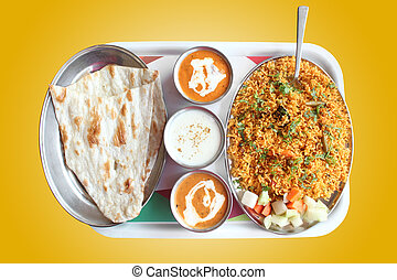 Indian biryani, butter naan with spicy curry and raitha on a...