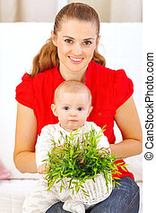 Baby playing with plant while sitting on mothers laps