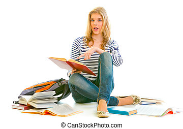 Shocked teen girl sitting on floor with schoolbag and pointing finger in open schoolbook isolated on white