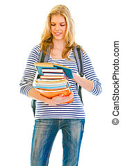 Smiling teen girl with pile of schoolbooks in hands reading isolated on white