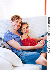 Happy young couple relaxing at home