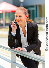 Smiling modern business woman leaning on railing and talking on mobile