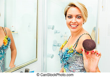 Cheerful pretty young woman in bathroom extends fluffy brush in camera
