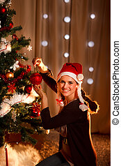 Beautiful woman hanging Christmas ball on Christmas tree