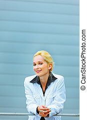 Smiling business woman leaning on railing at office building