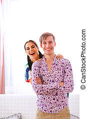 Cheerful young couple having fun at home