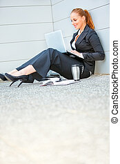 Smiling modern business woman sitting on floor at office...