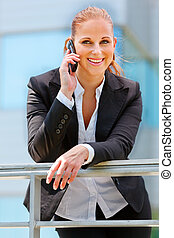 Portrait of smiling modern business woman leaning on railing...