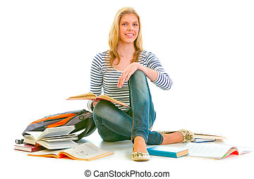 Cheerful teen girl sitting on floor among schoolbooks