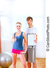 Healthy couple in sportswear showing clipboard with...