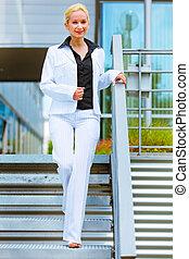 Smiling business woman walking down stairs - Smiling modern...